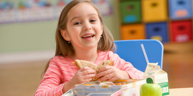 Girl (4-5) eating lunch, smiling, portrait